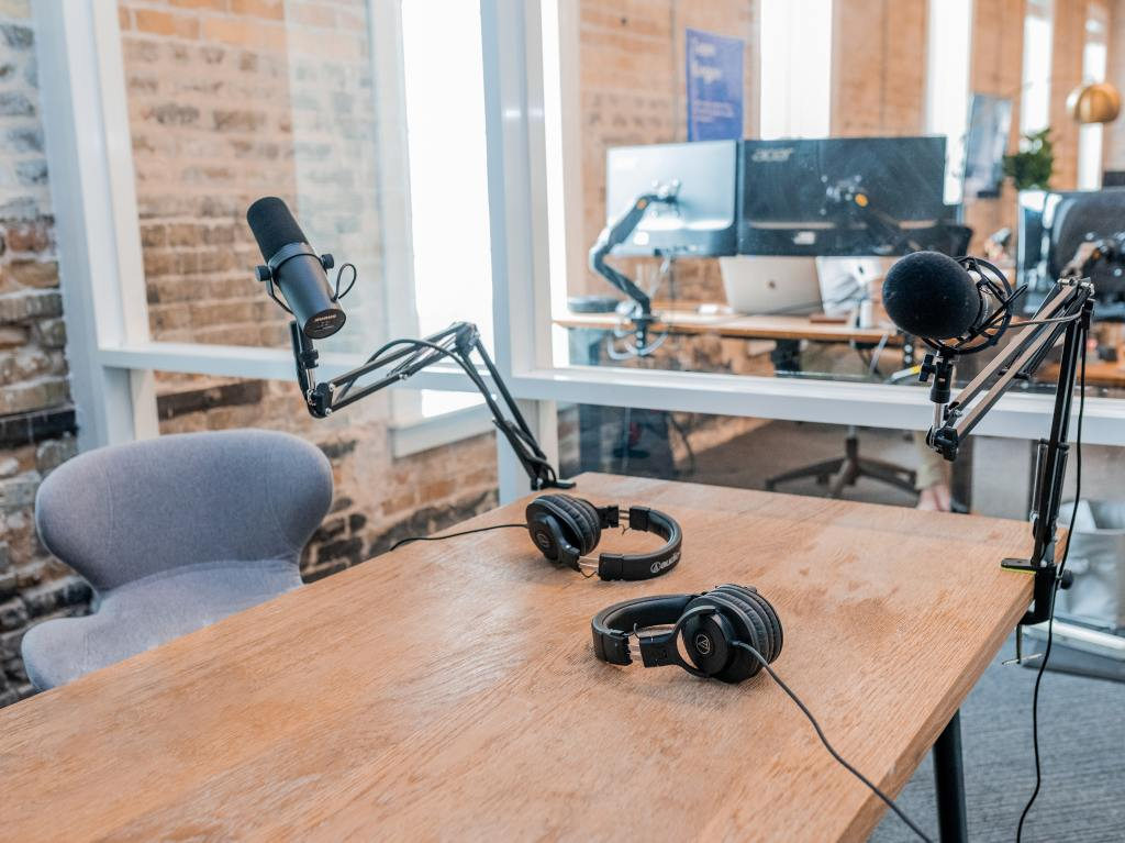 Podcasting microphone set up with a table, chair, and equipment