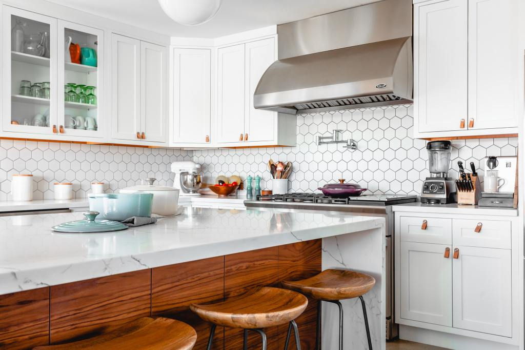 Modern kitchen with white fixtures, stainless steel hood, white tiled backsplash and quartz island