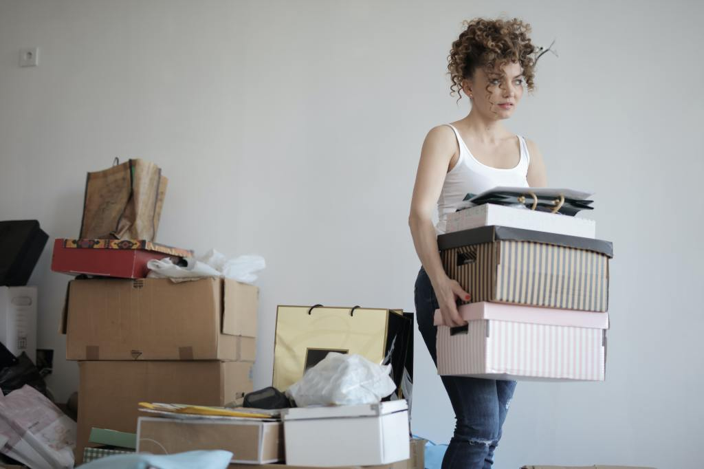 Woman moving boxes filled with packed items