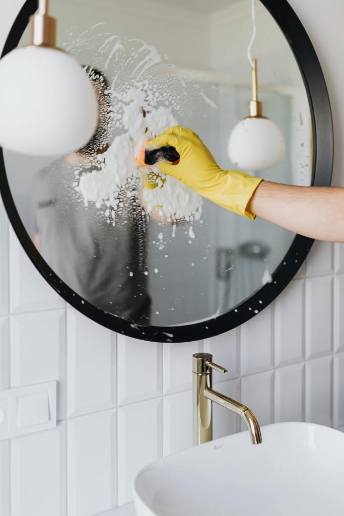 Man cleaning a mirror