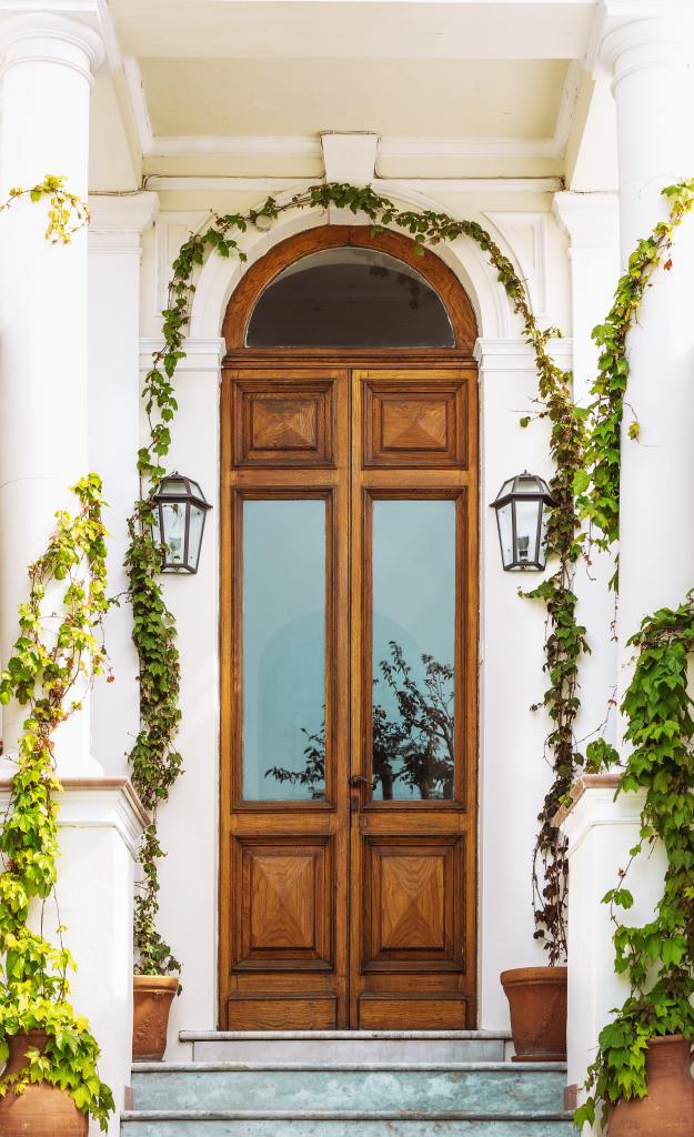 Welcoming entryway with towering wooden door with fresh greenery